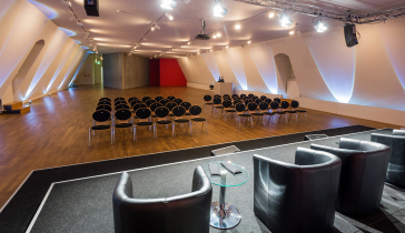 In the empty conference room, large black leather chairs with small round glass tables face rows of empty chairs