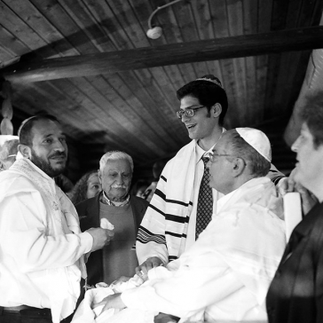 Black and white photography: Grandfather and father look at the mohel, the great-granduncle at the baby