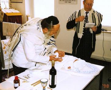 Älterer Mann mit Tallit beschneidet ein Baby, das auf einem Tisch liegt. Im Hintergrund steht ein weiterer Mann mit Tallit