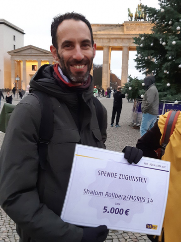 Man smiling at the camera, holding a check for 5,000 euros