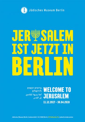 """Ausstellungsplakat mit Aufschrift """"Jerusalem ist jetzt in Berlin"""" in gelben Buchstaben auf blauem Hintergrund. Der Buchstabe 'u' in Jerusalem hat die Form einer Menora"""