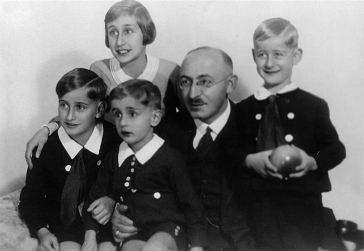 Black-and-white photo showing a man surrounded by his daughter and his three sons.