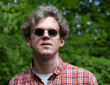 Porträt von Jonas Hauer mit kariertem Hemd, Sonnenbrille vor einem Baum