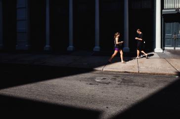 Auf einem Bürgersteig gehen sich eine junge Frau und ein Mann entgegen, beide blicken auf ihre Smartphonesauf ihre I