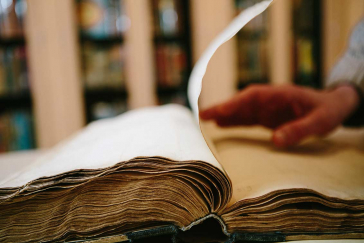 Hand turns over a page of an open thick, old book