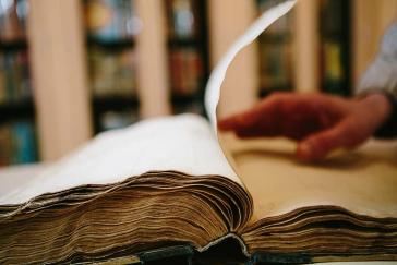 Hand blättert aufgeschlagenes dickes, altes Buch um