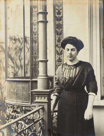 Schwarz-Weiß-Porträtfoto einer jungen Frau. Sie trägt ein hochgeschlossenes Kleid im Stil der 1910er Jahre und eine Hochsteckfrisur und steht vor einem Haus, dessen prächtige Fassadenverzierung im Hintergrund zu sehen ist.
