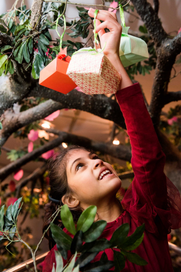 A girl hangs a pomegranate-shaped gift on a tree branch