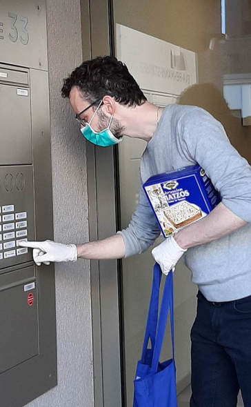 A man wearing a surgical face mask with a package of matzo under his arm rings a doorbell