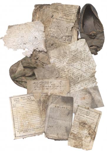 Verschiedene zerknitterte Schriftstücke mit hebräischen Buchstaben, ein Schuh und eine Tasche