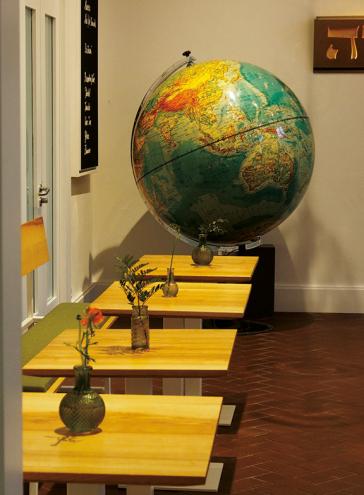 Blick ins Museumscafé mit Tischen, Stühlen und einem Globus