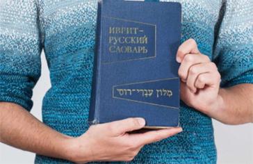 Hände halten ein Buch mit russischer und hebräischer Schrift darauf