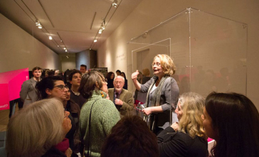 A woman stands at the opening of a showcase and talks to a crowd of visitors