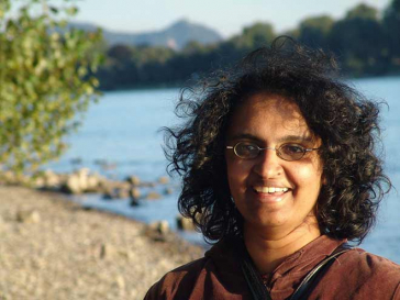 Porträt einer Frau, im Hintergrund Strand und Meer