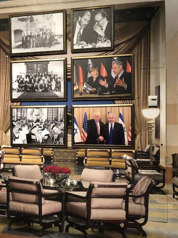 Wand mit sechs großformatigen, gerahmten Fotos. Im Vordergrund Sessel und Tische, der Raum wirkt wie eine Hotellounge