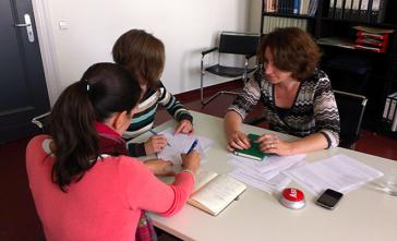 Drei Redakteurinnen sitzen um einen Tisch und diskutieren.