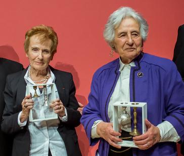 Zwei lächelnde Damen präsentieren die Auszeichnung