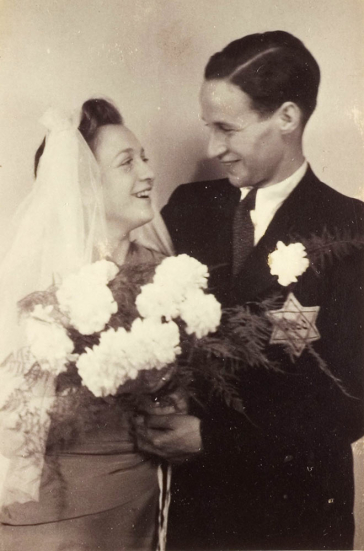 Black and white photograph of a couple with a bouquet of flowers and a veil,  a yellow badge on his jacket.