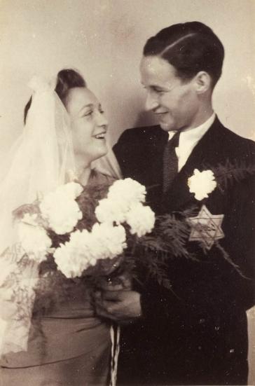 """Schwarz-weiß-Fotografie eines Paares mit Blumenstrauß und Schleier, an seinem Jacket ein """"Judenstern"""""""