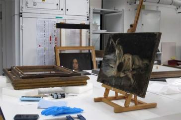 Gemälde auf einer Staffelei auf einem Tisch, davor Handschuhe und Werkzeuge