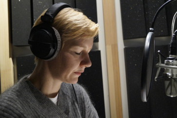 The actress and speaker Sandra Hüller sits with headphones in front of the microphone in the recording studio