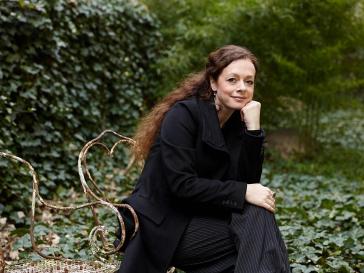 Porträt Shelly Kupferberg, in einem Garten sitzend, lächelnd, das Kinn auf die Hand gestützt
