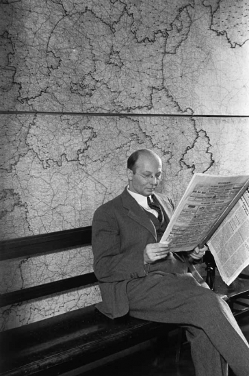 Black and white photography: a seated man reading an issue of the C.V. newspaper. There is a map on the wall behind him.