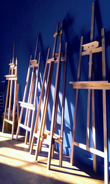 Foto von Staffeleien, die an einer blauen Wand lehnen.