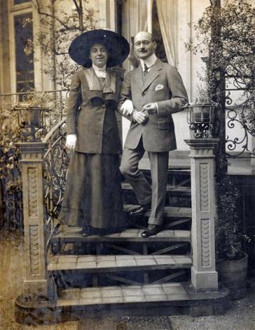 Eine Frau und ein Mann stehen gemeinsam auf einer Treppe vor einem Haus. Sie trägt einen riesigen Hut und Handschuhe zum dunklen Kleid und hat sich bei ihm eingehakt, er trägt einen Anzug mit Einstecktuch.