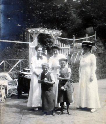 Drei Damen in weißen Kleidern, eine mit großem Hut, stehen vor einem Eingangstor. Vor ihnen stehen zwei barfüßige Jungs mit Tennisbällen in den Händen.