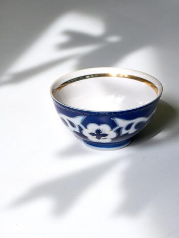 Foto einer blau-weiß gemusterten Teeschale mit goldenem Rand