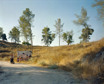 Photography: View into a landscape, at the left edge of the picture there is a family in front of a poster, on which people a