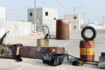 Tin barrels and other sheet metal objects and a car tire on a road along white flat-roofed houses