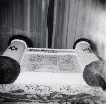 Black-and-white photo of a cake shaped like a Torah scroll on a table with a lace tablecloth