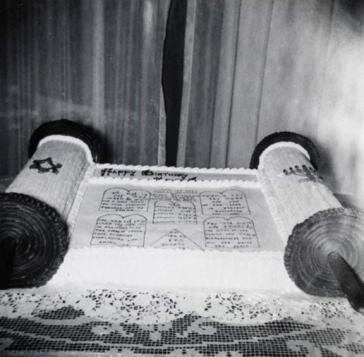 Schwarz-weiß-Foto eines Kuchens in Form einer Tora-Rolle auf einem Tisch mit Spitzentischdecke