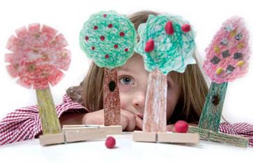 Ein Kinderkopf hinter vier aus Pappe gebastelten Bäumen mit Wäscheklammern als Ständer