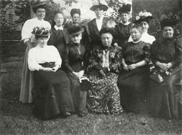 Group picture of eleven women with fancy hats in a garden