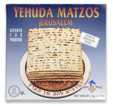 """Abgebildet ist auf der Vorderseite eine Photographie eines Brottellers, auf dem einige Mazzot liegen und dessen Tellerrand der zweite Teil des Segensspruchs für Brot oder Mazzot (hebr.) """"Ha-Mozi Lechem min ha-Aretz"""" (...der, der Brot aus der Erde gebracht"""