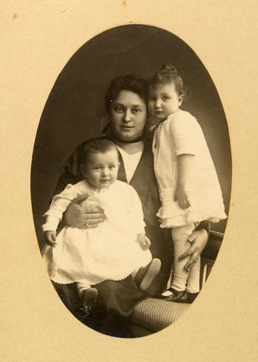 Ovale Studioaufnahme einer Frau, die ein Kleinkind auf dem Schoß hat, ein etwas größeres Kind steht neben ihr auf einem Stuhl