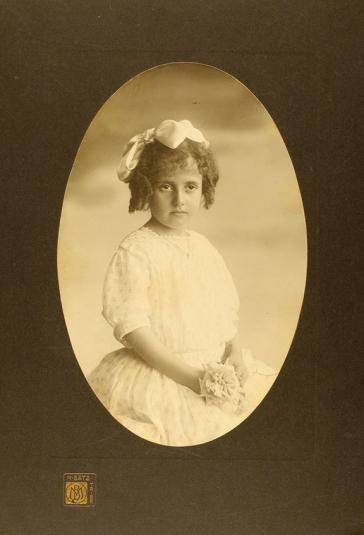 Studioaufnahme eines Mädchens in weißem Kleid, mit Schleife im Haar und Stoffblume in der Hand