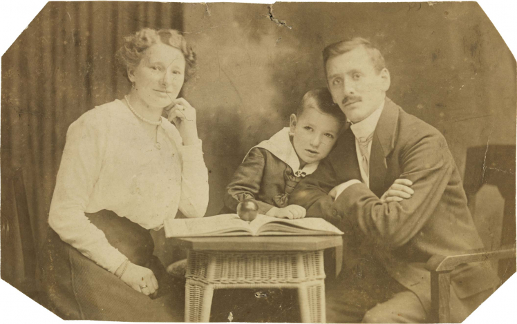 Black-and-white photograph: couple with son in the middle, studio photograph