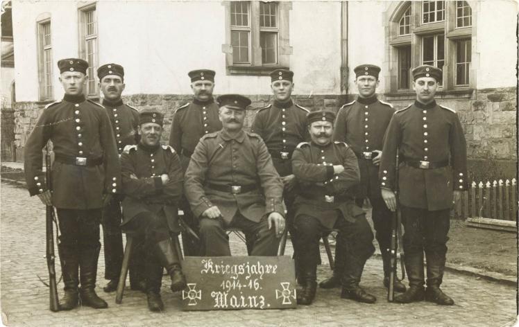 Schwarz-weiß-Foto: Neun uniformierte Soldaten vor einer Kaserne