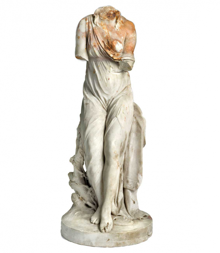 Female statue with traces of rust, missing the head