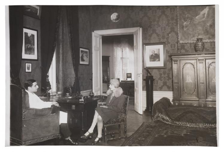 Schwarz-Weiß-Fotografie einer Frau und eines Mannes, die sich in Sesseln gegenüber sitzen