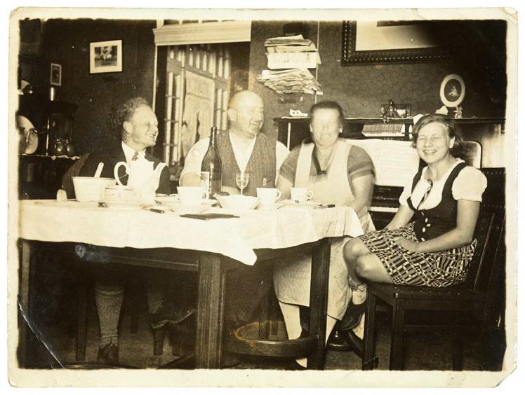 Schwarz-Weiß-Foto: vier lachende Personen an einem gedeckten Esstisch, die Gesichter großteils verschwommen