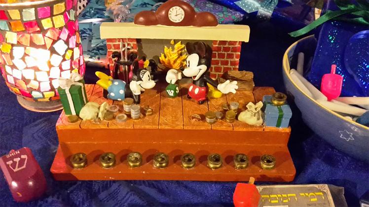 Der im Text beschriebene Chanukka-Leuchter auf einem Tisch mit Geschenken, Lampe und Dreidel