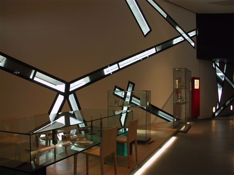 A display case arranged like a Shabbat table inside the Libeskind Building in front of the window slits