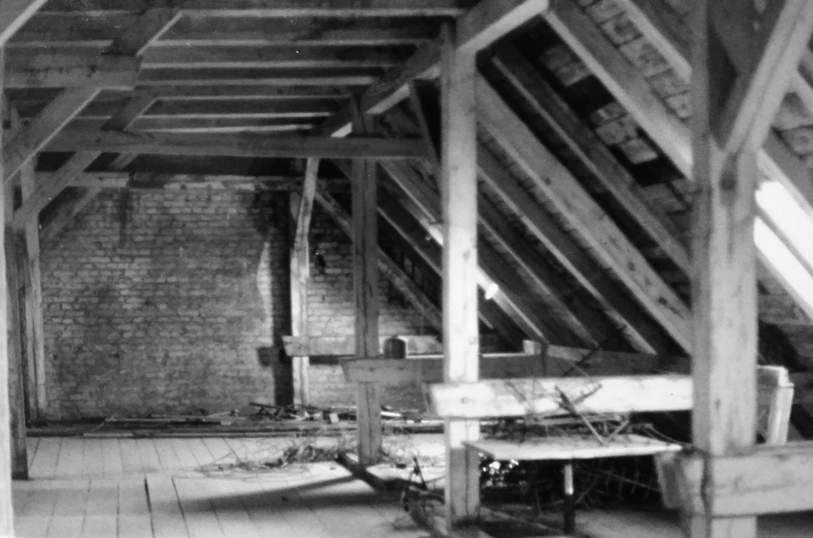 Black-and-white photograph: Attic with wooden beams and a brick wall