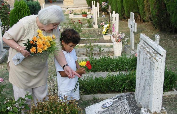 Filmstill: Eine ältere Frau und ein Junge stehen mit Blumen vor einem Grab