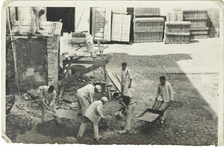 Seven men in working clothes and with wheelbarrow, shovels and other equipment (black and white photo)